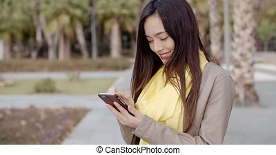Stylish woman checking a message on her mobile - Stylish...