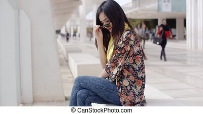 Thoughtful young woman sitting on a promenade