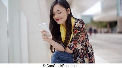 Chic young woman reading a mobile message - Chic young woman...