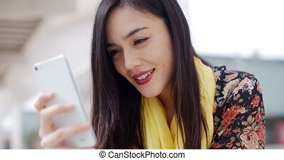 Young woman reading a message on a mobile - Attractive...