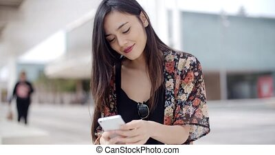 Young woman sitting reading a text message on her mobile...