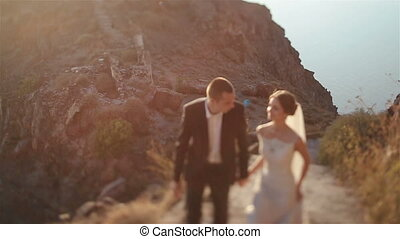 Married couple, bride and groom, walking on mountain volcano...