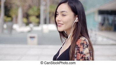 Young woman walking listening to music on earphones attached...
