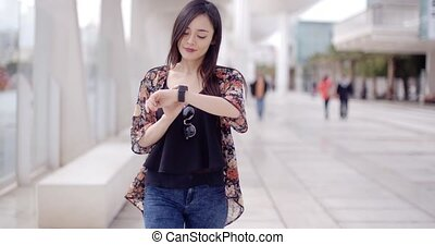 Young woman checking her wristwatch - Young woman in a smart...
