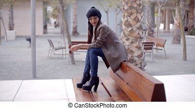 Fashionable young woman sitting waiting on a bench -...