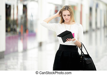 Young female out of money checking her purse in disbelief -...