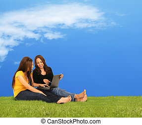 Girls Enjoying Laptop Outdoor - two girls looking at laptop...