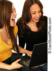 Teens Having Fun With Internet - two young girls playing...
