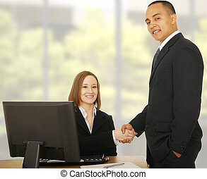 Business People Smile At Camera While Shaking Hand - two...