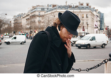 Thoughtful Bearded Man Wearing Hat Smoking on the Street in...