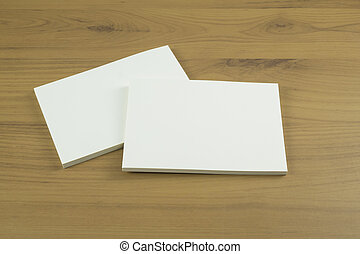 Photo of blank business cards with soft shadows on light wooden background.