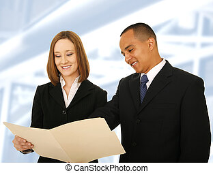 Business Team Reviewing Folder - two business people looking...