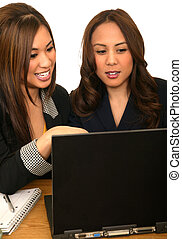 Women Business Team Pointing At Laptop - two business women...