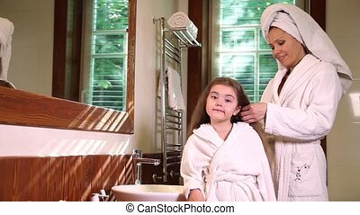 Mother combing hair of her daughter