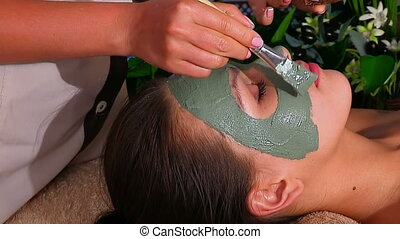 Woman with clay facial mask in beauty spa. Hands of...
