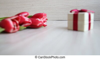 red-white tulips and gift box with bow on white table -...