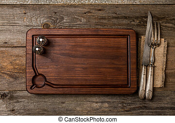 Chopping cutting board, seasonings and meat fork and knife