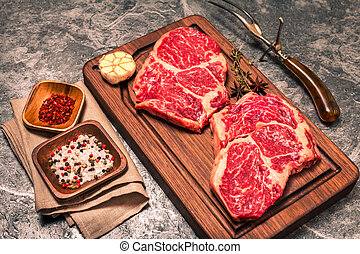 Raw fresh marbled meat Steak with seasonings on grey...