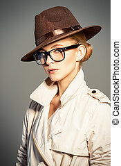 female agent - Fashion model posing at studio in a coat, hat...