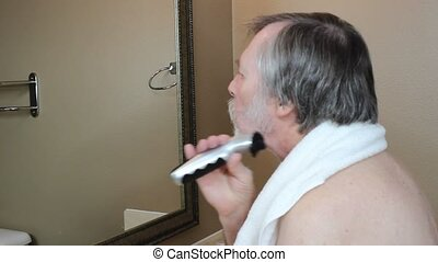 Shaving off a beard - A senior man shaves off his beard with...