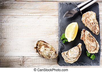 Fresh oysters with lemon on stone plate. Food background...