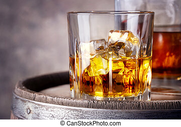 Faceted glass of whiskey with ice on wooden barrel