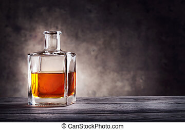 Square decanter of brandy on a dark background
