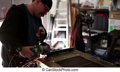 Man Grinding metal in home workshop