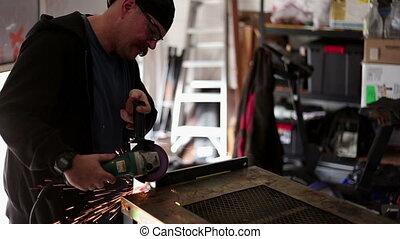 Man Grinding metal in home workshop