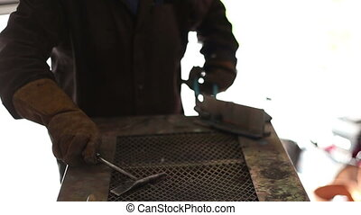 Welder cleaning up weld surface - Welder cleaning up weld...