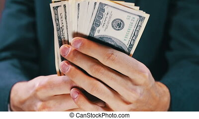 Businessman Counts Money in Hands - Businessman counts...