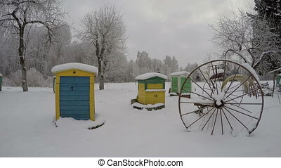 beehives in winter and horse rake - Three colorful beehives...