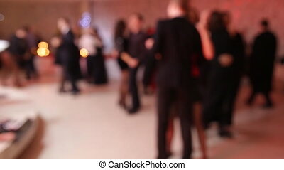 Group of people dancing in a banquet hall with live music