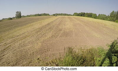 Tractor plowing field on sunny autumns day by the forest,...