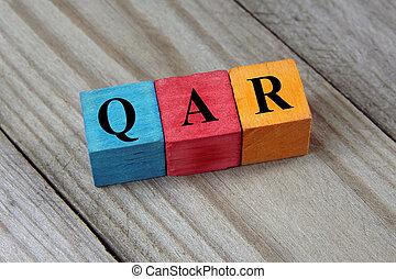 QAR (Qatari Riyal) sign on colorful wooden cubes
