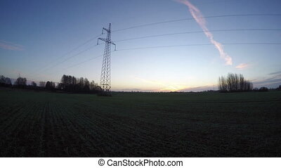 electricity pole during sunrise - Young green wheat field...