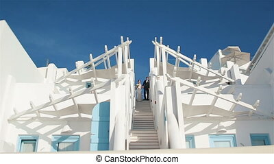 Newlywed wife and husband come down white stairs from...
