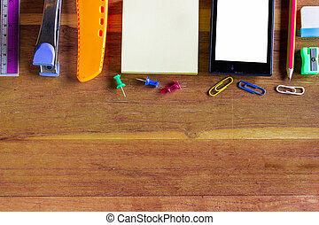 Assorted Office Supplies such as notebooks, cutter, mobile phones, Thumbtacks and Clips on Top of Wooden Desk with Copy Space.