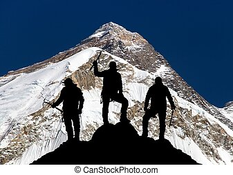Mount Everest and silhouette of three climbers - Mount...
