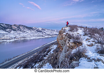 hiking Colorado before sunrise - male hiker on cliff above...