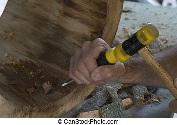 wood working - Man carving inside a tree stump with a chisel...