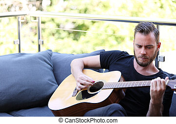 Man with acoustic guitar - An attractive man in his 20s...