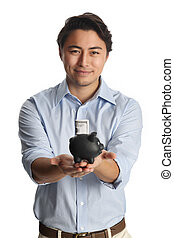 Handsome man with piggy bank - An attractive man in his 20s,...