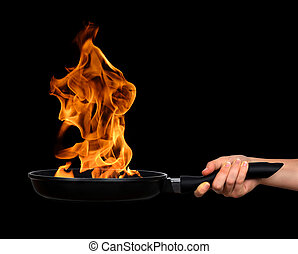 frying pan with flames - Woman's hand holding a frying pan...