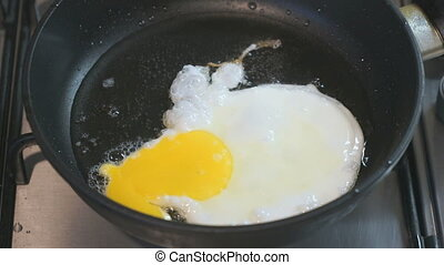 Frying eggs in a skillet Skillet stands on the hob Closeup -...