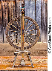Old spinning wheel  in the background of wood
