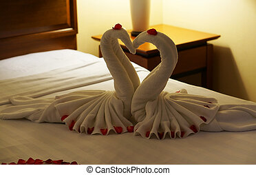 Two swans made from towels on honeymoon bed for surprise...