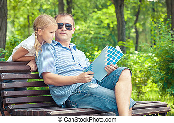 Father and daughter playing at the park on bench at the day...