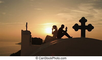 Happy married couple prays on the top of the hill at sunset sky background