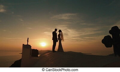 Groom and bride silhouette kissing on church roof at sunset sky background